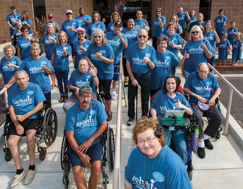 A variety of people wearing blue aphasia center shirts smiling and looking into camera